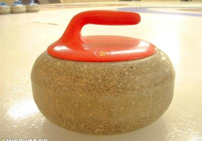 Pierre de curling en granit avec poignée rouge.